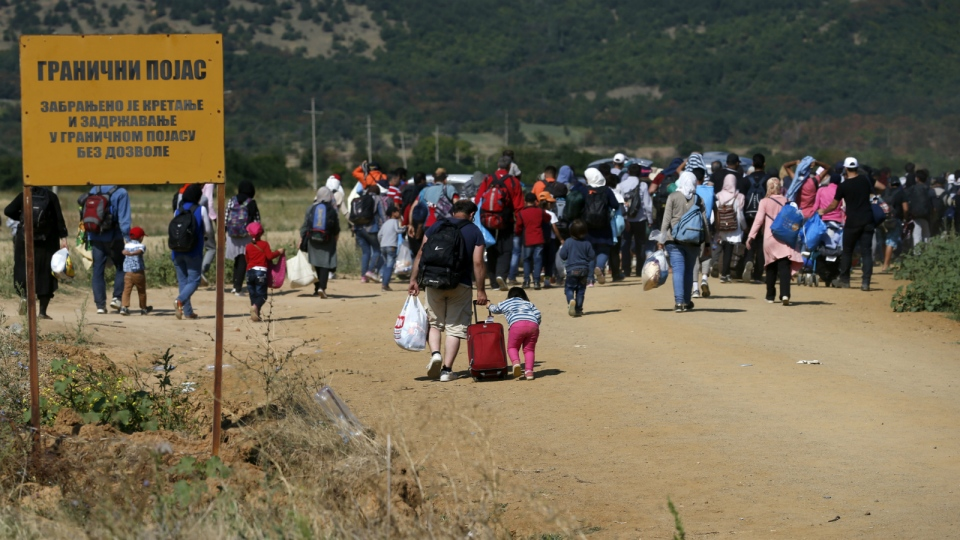 Migrants walking from Macedonian border into Serbia, passing a Serbian border sign, near the village of Miratovac, Serbia on Aug. 24, 2015. (AP / Darko Vojinovic)