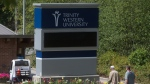 Two men walk past a sign at Trinity Western University in Langley, B.C., on Monday, Aug. 24, 2015. (Darryl Dyck / THE CANADIAN PRESS)