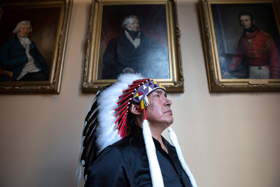 Grassy Narrows First Nation Chief Roger Fobister is pictured in front of portraits of former lieutenant-governors of Upper Canada, which hang in the Ontario Legislature, after an accord was signed by Ontario Regional Chief Isadore Day and Ontario Premier Kathleen Wynne in Toronto on Monday, Aug. 24 2015. (Chris Young/The Canadian Press)