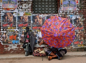 A Bangladeshi man fixes an umbrella as he sits in front of the posters of a film 'Rana Plaza' pasted on the wall of a movie theatre in Dhaka, Bangladesh, Tuesday, Aug. 25, 2015. (AP Photo/A.M. Ahad)