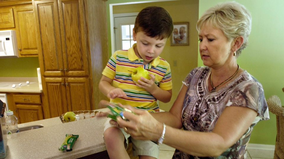A mother checks the label of a snack for peanuts in Brunswick, Ga., on Tuesday, Aug. 4, 2008. (AP Photo/Stephen Morton)