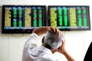 A Chinese stock investor reacts near a display for stock prices at a brokerage house in Qingdao in eastern China's Shandong province Tuesday, Aug. 25, 2015. Chinese stocks tumbled again Tuesday after their biggest decline in eight years while most other Asian markets rebounded from a day of heavy losses. (Chinatopix via AP)