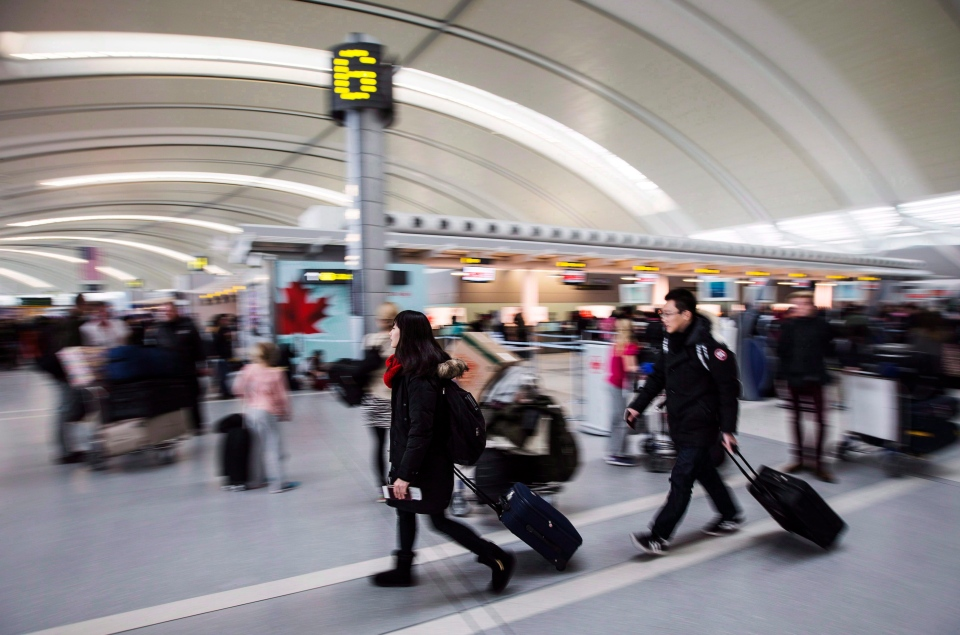 People carry luggage at Pearson International Airport in Toronto, Dec. 20, 2013. (Mark Blinch / THE CANADIAN PRESS)