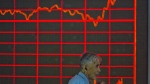 A Chinese investor walks past a display of the Shanghai Composite Index at a brokerage in Beijing on Aug. 27, 2015. (AP / Ng Han Guan)