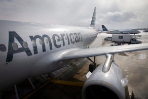 In this Feb. 26, 2014 file photo, an American Airlines Flight Airbus A319 is parked at a gate at Philadelphia International Airport as a US Airways plane taxis in the background, in Exton, Pa. (Alejandro A. Alvarez/Philadelphia Daily News via AP)