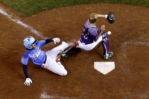 Pearland, Texas catcher Ryan Farmer can't handle the relay throw as Bonita, Calif.'s Nate Nankil (14) scores during the third inning of a U.S. elimination baseball game at the Little League World Series in South Williamsport, Pa., Thursday, Aug. 27, 2015. (AP/Gene J. Puskar)