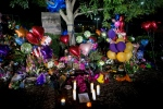 A makeshift memorial for WDBJ-TV reporter Alison Parker and cameraman Adam Ward gathers by a tree near the station Thursday, Aug. 27, 2015, in Roanoke, Va. (Erica Yoon/The Roanoke Times via AP)