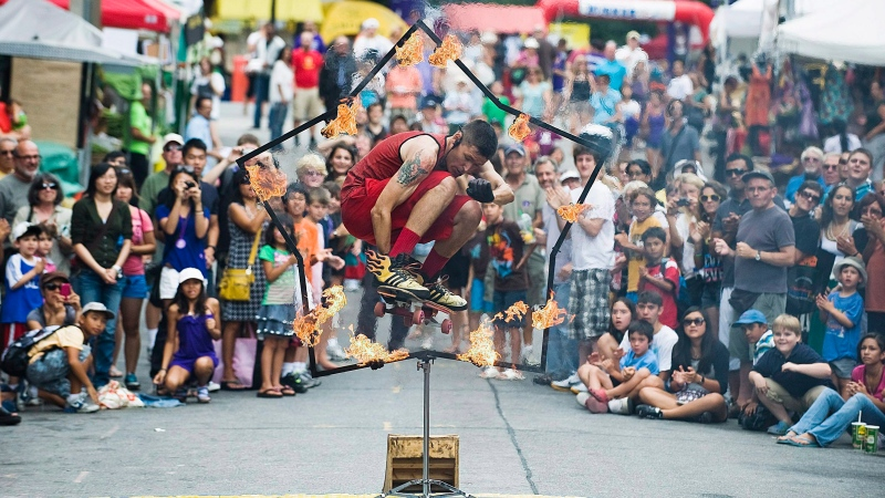 Brant Matthews, aka The Fire Guy jumps through a flaming hoop on his skateboard during the opening day of the Scotiabank BuskerFest in Toronto on Thursday August 25, 2011. THE CANADIAN PRESS/Aaron Vincent Elkaim