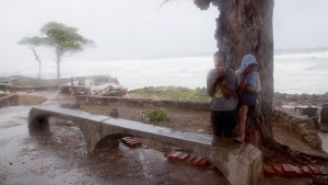 A couple of people take refuge behind a tree against the strong winds of Tropical Storm Erika, as it approaches Santo Domingo, in the Dominican Republic, Friday, Aug. 28, 2015. (AP / Tatiana Fernandez)