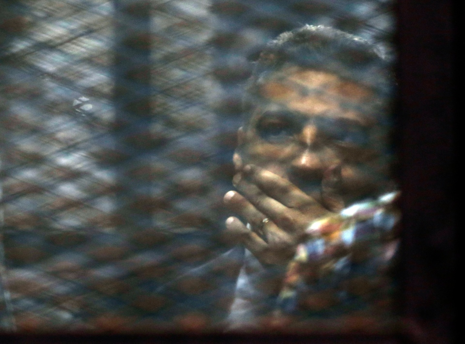 Canadian Al-Jazeera English journalist Mohamed Fahmy, listens to his verdict in a soundproof glass cage inside a makeshift courtroom in Tora prison in Cairo, Egypt, Saturday, Aug. 29, 2015. (AP / Amr Nabil)
