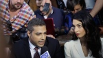 Canadian Al-Jazeera English journalist Mohammed Fahmy, left, his lawyer Amal Clooney and his Egyptian colleague Baher Mohammed, at top left, speak to media before their verdict in a courtroom in Tora prison in Cairo, Egypt, Saturday, Aug. 29, 2015. (AP / Amr Nabil)