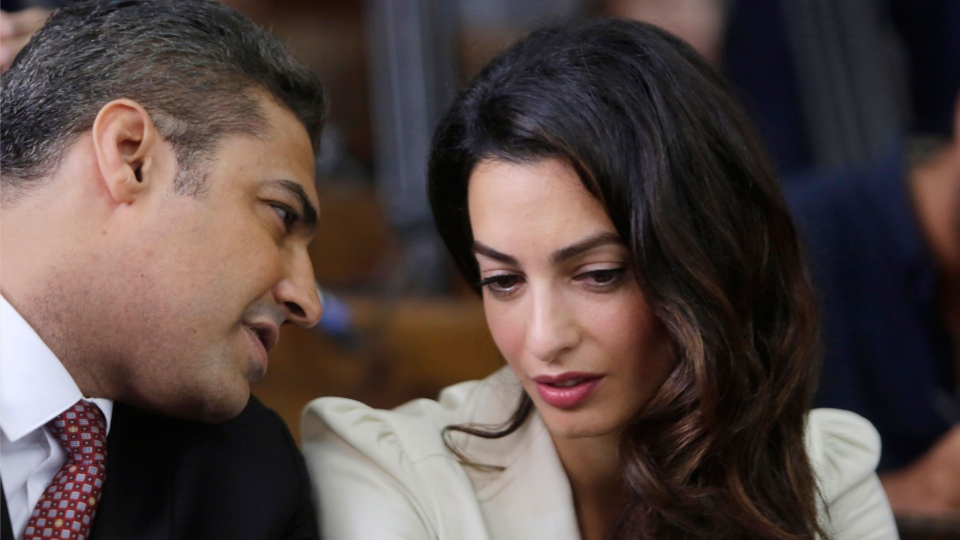 Canadian Al-Jazeera English journalist Mohammed Fahmy, left, talks to human rights lawyer Amal Clooney before his verdict in a courtroom in Tora prison in Cairo, Egypt, Saturday, Aug. 29, 2015. (AP / Amr Nabil)