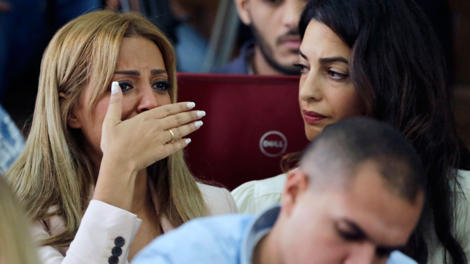 Marwa Fahmy wife of Canadian Al-Jazeera English journalist Mohammed Fahmy, bursts into tears, as she is watched by human rights lawyer Amal Clooney, after the verdict in a courtroom in Tora prison in Cairo, Egypt, Saturday, Aug. 29, 2015. (AP / Amr Nabil)