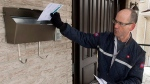 Letter carrier Richard Autotte delivers mail in the east end of Montreal Thursday, March 5, 2015. Police are investigating a series of robberies on letter carriers by thieves who have been taking the carriers keys to community and apartment mailboxes. (Ryan Remiorz/THE CANADIAN PRESS)