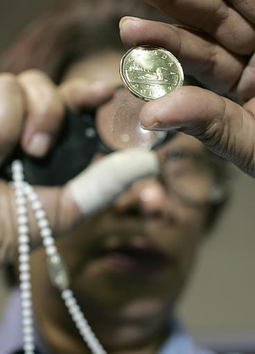 A worker at the Royal Canadian Mint checks the quality of loonies after they are pressed in Winnipeg on Tuesday, May 2, 2006. (CP PHOTO/Marianne Helm)
