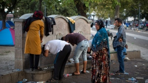Migrants wash themselves at public water taps in a park in Belgrade on Monday, Aug. 31, 2015. (AP / Santi Palacios)