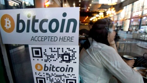 A Bitcoin ATM sticker is on the window of a shop in downtown Vancouver, on Oct. 28, 2013. (THE CANADIAN PRESS/Jonathan Hayward)