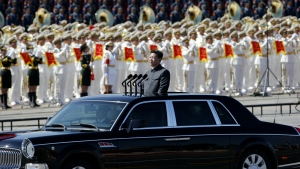 Chinese President Xi Jinping stands in a car to review the army during a parade commemorating the 70th anniversary of Japan's surrender during the Second World War held in front of Tiananmen Gate in Beijing, pm Sept. 3, 2015.