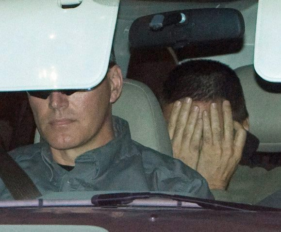 Hassan Diab, right, covers his face as he is escorted from the Ottawa Courthouse in Ottawa on Friday, Nov. 14, 2008. (Sean Kilpatrick / THE CANADIAN PRESS)
