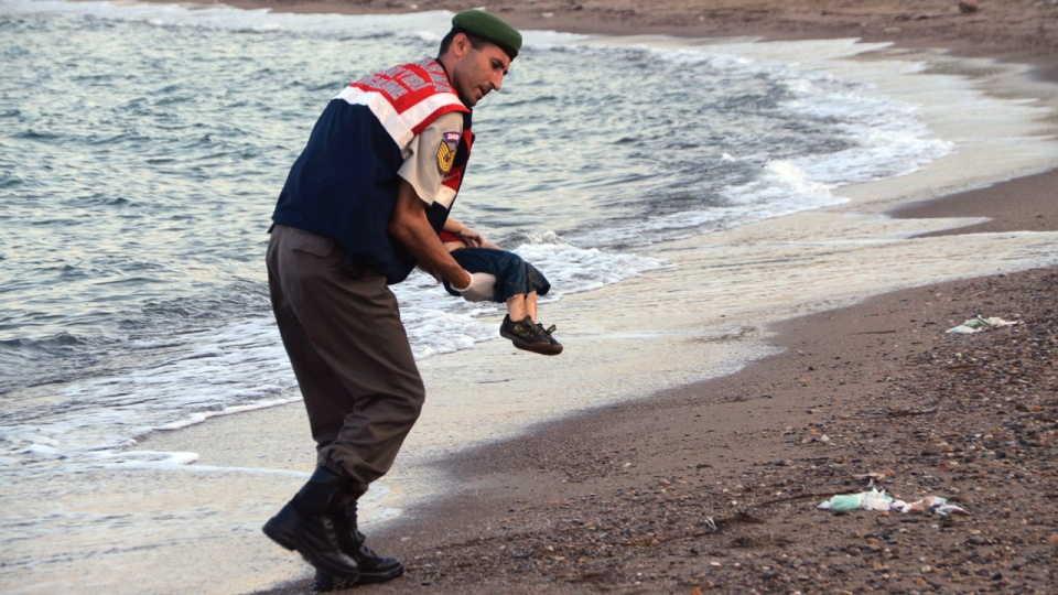 A paramilitary police officer carries the lifeless body of a migrant child identified as Alan Kurdi, after boats carrying him and many other migrants capsized near the Turkish resort of Bodrum, on Sept. 2, 2015. (THE CANADIAN PRESS / AP / DHA)