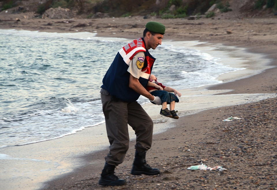 GRAPHIC WARNING: This photograph is of a young boy who died, an image readers may find distressing. A paramilitary police officer carries the lifeless body of a migrant child, lifting it from the sea shore, near the Turkish resort of Bodrum, Turkey, early Wednesday, Sept. 2, 2015. (AP Photo / DHA)