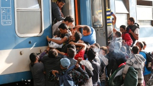 Migrants struggle to board a train at the railway station in Budapest, Hungary, Thursday, Sept. 3, 2015. (AP / Frank Augstein)