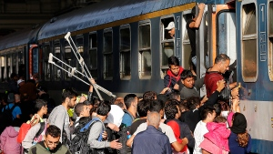 Migrants try to board a train at the railway station in Budapest, Hungary, Thursday, Sept. 3, 2015. (AP / Frank Augstein)