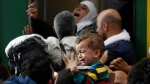 A young child cries as hundreds of migrants try to board a train at the Keleti Railway Station in Budapest, Hungary, Thursday, Sept. 3, 2015. (AP / Petr David Josek)