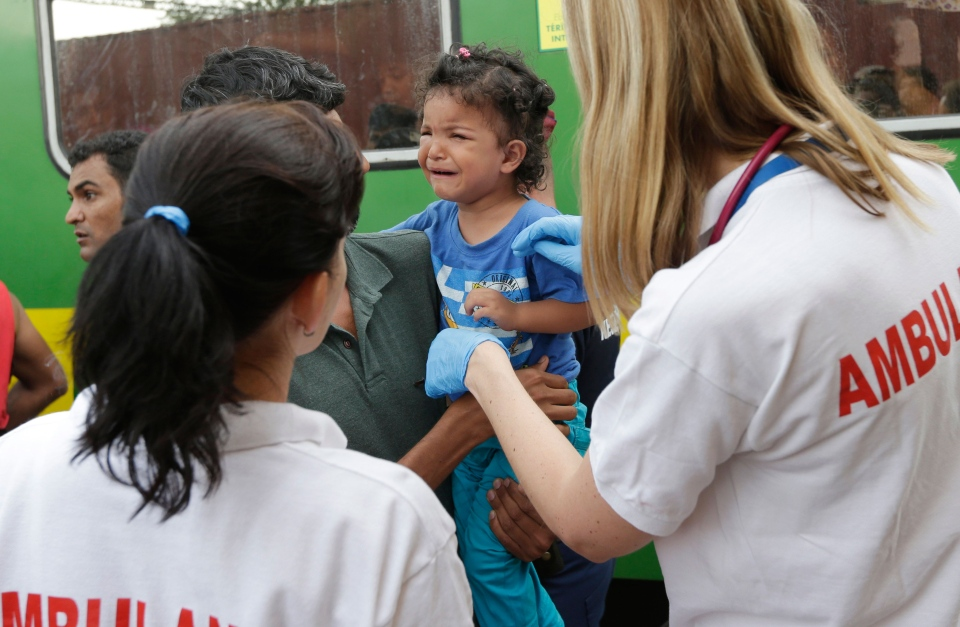 Medical staff treat a small child outside a train with migrants that was stopped in Bicske, Hungary, Thursday, Sept. 3, 2015. (AP / Petr David Josek)