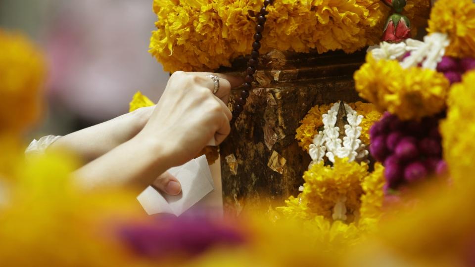 A visitor applies gold leaf as a tribute to Phra Phrom, the Thai interpretation of the Hindu god Brahma, at the Erawan Shrine in Bangkok, Thailand on Sept. 3, 2015. (AP / Sakchai Lalit)