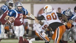 Montreal Alouettes' quarterback Tanner Marsh, left, is tackled by BC Lions' Jabar Westerman during second half CFL football action in Montreal on Sept. 3, 2015. (Graham Hughes / THE CANADIAN PRESS)