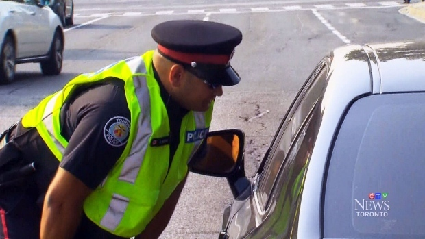 A Toronto police officer speaks to a driver in Toronto on Tuesday, Sept. 1, 2015.