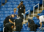 In this Thursday, Sept. 3, 2015, photo, police officers and fire officials inspect the remains of a drone that crashed into an empty section of seats at the U.S. Open tennis tournament in New York. (AP / Kathy Willens)