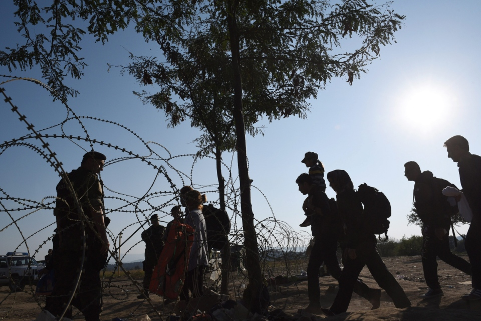 A Macedonian police officer stands at the border line as refugees cross the border from Greece to Macedonia, at the town of Idomeni, northern Greece, Sunday, Aug. 30, 2015. (AP/Giannis Papanikos)