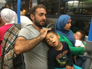 Migrants board a bus in Budapest as they travel to the Austrian border on Sept. 9, 2015. (CTV / Paul Workman)