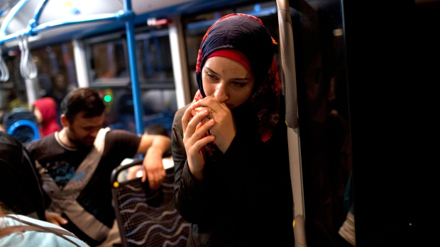 A woman pauses on a bus provided by Hungarian authorities for migrants and refugees at Keleti train station in Budapest, Hungary, Saturday, Sept. 5, 2015. (AP / Marko Drobnjakovic)