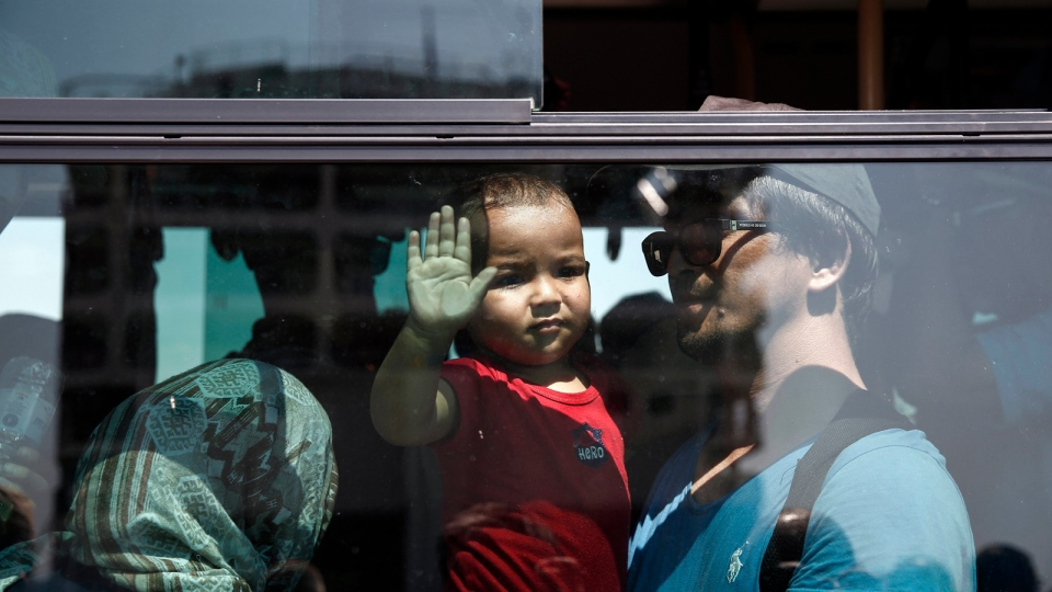 A baby looks out from a bus transporting migrants and refugees to a metro station, after their arrival from the northeastern Greek island of Lesbos to the Athens' port of Piraeus, Greece, on Saturday, Sept. 5, 2015. (AP / Yorgos Karahalis)
