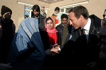 Foreign Affairs Minister Peter MacKay, right, shakes hand with an Afghan woman, who receives money from the micro-finance section of a Canadian-funded Vocational Training Center.  (AP Photo, Musadeq Sadeq)