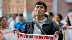 A demonstrator carries a sign that reads, 'They took them alive, return them alive,' in reference to 43 missing students from the Ayotzinapa rural teachers college, during a march in Mexico City March 10, 2015. (AP / Eduardo Verdugo)