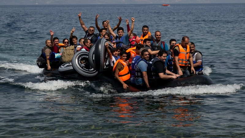 Syrian refugees arrive at Lesbos, Greece, aboard a dinghy after crossing from Turkey, on Sept. 7, 2015. (Petros Giannakouris / AP)