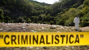A forensic examiner walks along a garbage-strewn hillside above a ravine where examiners are searching for human remains in densely forested mountains outside Cocula, Guerrero state, Mexico, Oct. 28, 2014. (AP / Rebecca Blackwell)