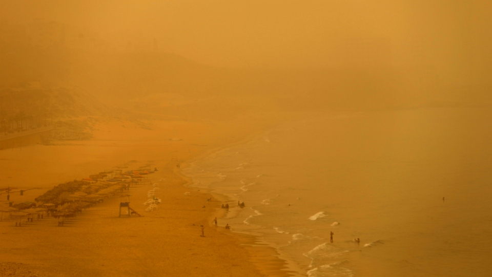 People swim at the public beach of Ramlet al Bayda during a sand storm in Beirut, Lebanon, Tuesday, Sept. 8, 2015. (AP / Hassan Ammar)