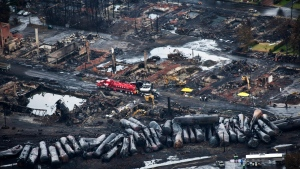 Workers comb through debris after a train derailed causing explosions of railway cars carrying crude oil in Lac-Megantic, Que., Tuesday, July 9, 2013. (AP / The Canadian Press, Paul Chiasson, File)