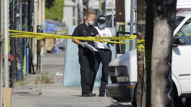 Los Angeles Police Department investigators work at a crime scene, where three children have been found dead inside a car parked outside an elementary school while a man found with them is in critical condition in South Los Angeles on Sept. 9, 2015. (AP / Nick Ut)