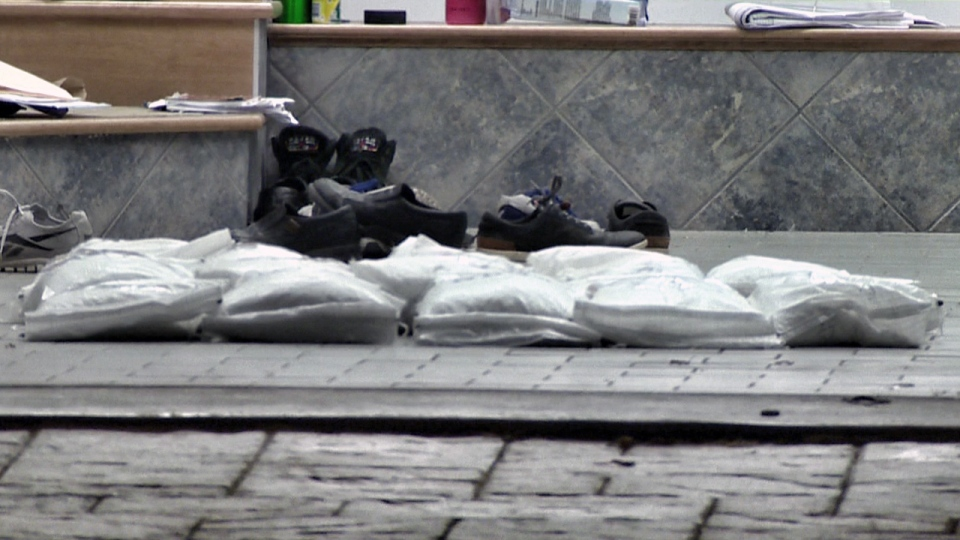 Piles of silver ingots wrapped in plastic lie in a garage being searched by police (CTV Montreal/Cosmo Santamaria)