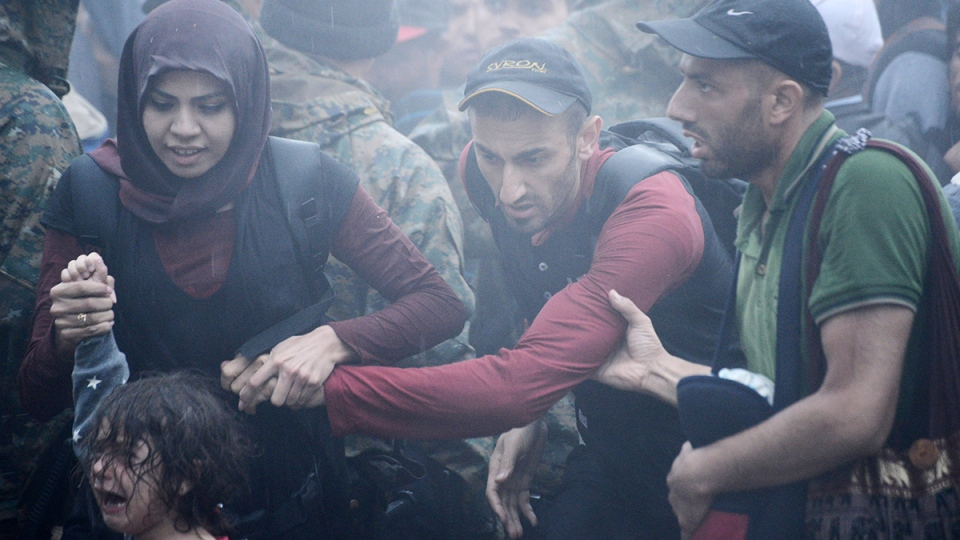 A girl cries as refugees and migrants try to cross the borders in heavy rainfall from the northern Greek village of Idomeni to southern Macedonia, Thursday, Sept. 10, 2015. (AP / Giannis Papanikos)