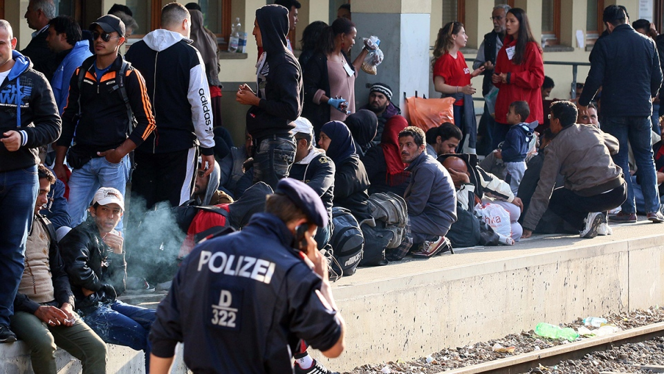 Migrants and refugees wait for a train from Vienna to Munich at the Westbahnhof train station in Vienna, Thursday, Sept. 10, 2015. (AP / Ronald Zak)