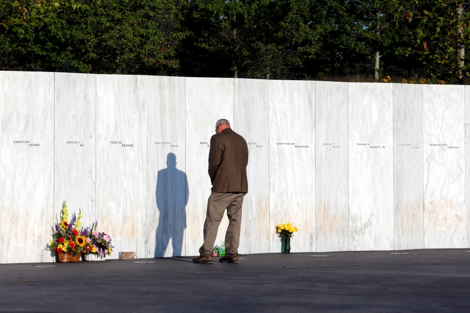 A visitor pauses at the Wall of Names at sunrise before a Service of Remembrance at the Flight 93 National Memorial in Shanksville, Pa, Friday, Sept. 11, 2015. (AP / Gene J. Puskar)