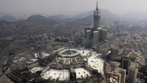 Abraj Al-Bait Towers with the four-faced clocks stands over the holy Kabaa, as Muslims encircle it inside the Grand Mosque in Mecca, Saudi Arabia, onOct. 5, 2014. (Khalid Mohammed / AP)