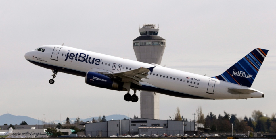 In this April 23, 2013, file photo, a JetBlue plane takes off in view of the air traffic control tower at Seattle-Tacoma International Airport, in Seattle. (Elaine Thompson, File/AP Photo)
